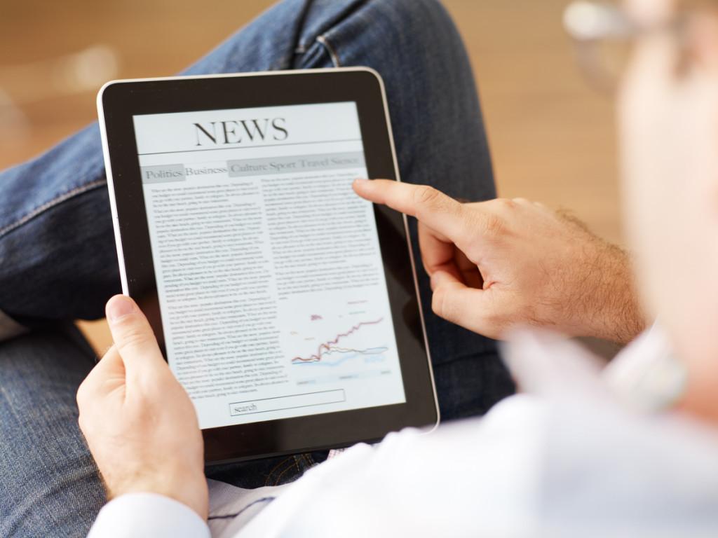 Man reading the newspaper on digital tablet