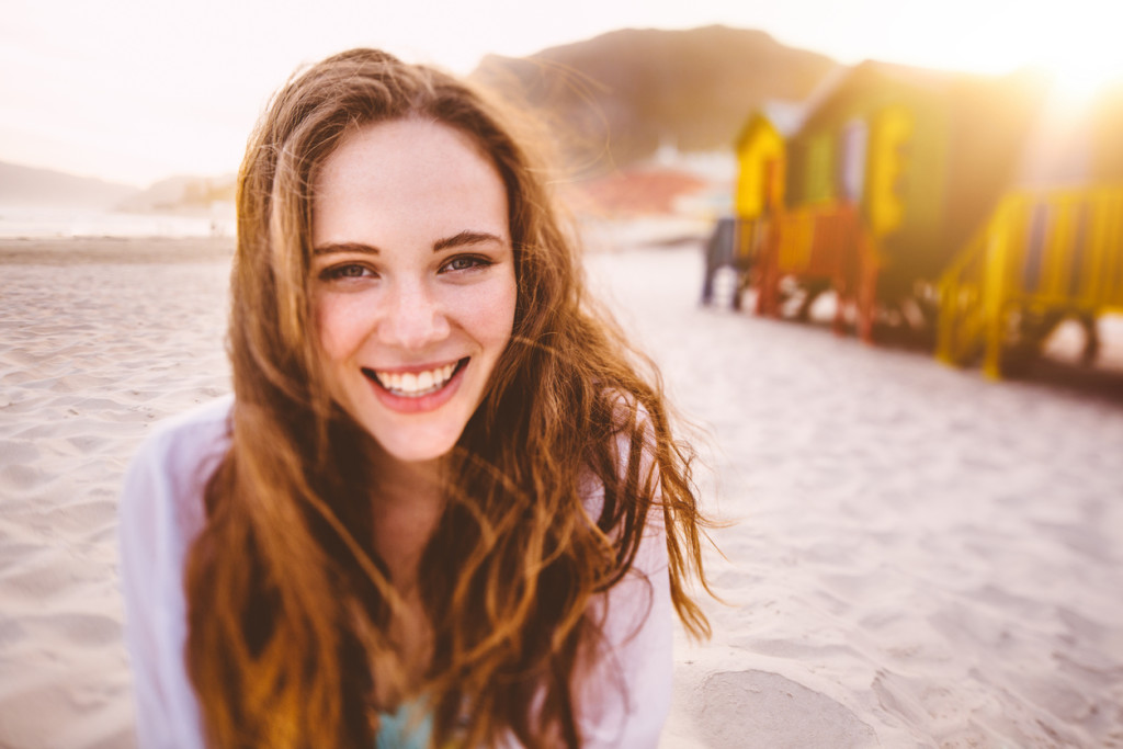 Happy girl smiling in front of colourful beach huts