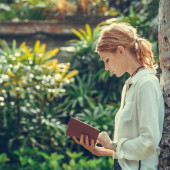 Portrait of a young woman reading a book in the park