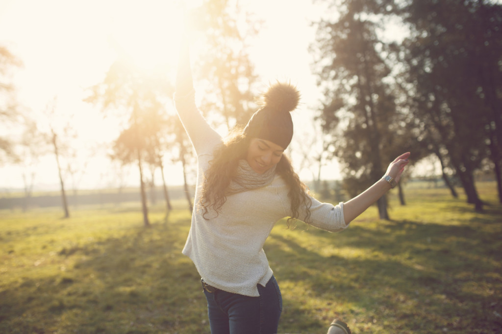 Beautiful caucasian young woman with a hat and scarf dancing through the grass in autumn sunny day, enjoying