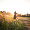 A beautiful woman is walking through a meadow. She's alone in a peaceful natural setting, walking towards the setting sun. The meadow is located in Sandy, Oregon.