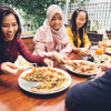 Friends Enjoying Meal In Outdoor Restaurant