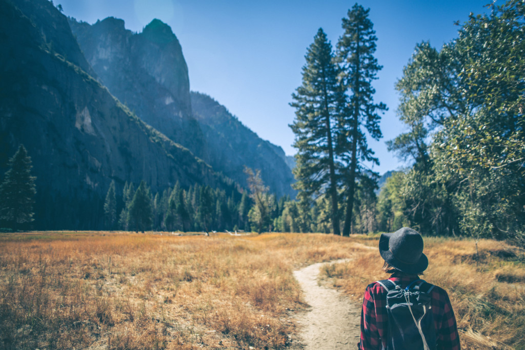 A shot of a young woman hiking down a path in a majestic landscape.