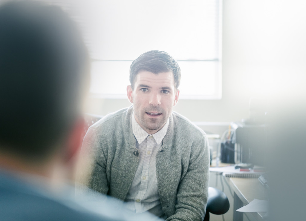 Businessman talking to male colleague at desk