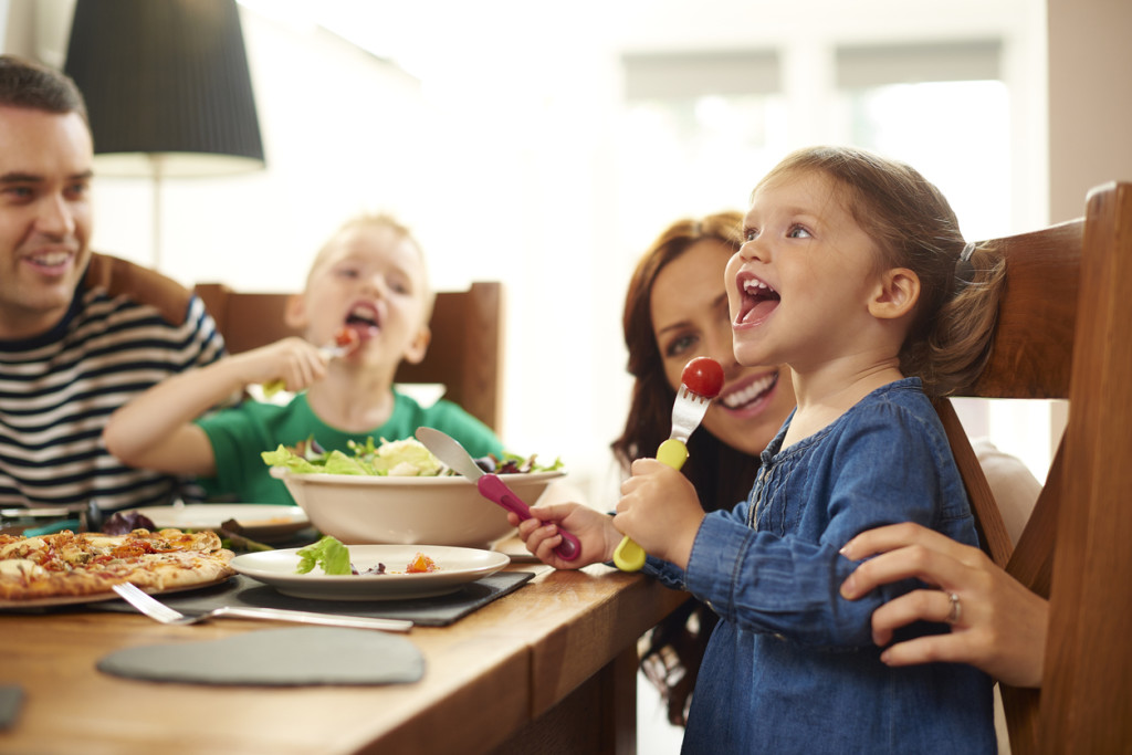 a young family of four sit at the dining table and eat pizza and salad. Mum helps her little girl with her meal , as she cheekily stuffs a whole tomato into her mouth .