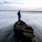 Man on a rock at the beach watching the waves crash, long exposure