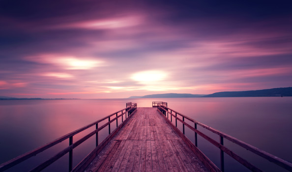 long exposue view of purple sky and wooden pier during sunset. reflections over sea. taken in Canakkale, Turkey.