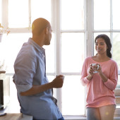 Shot of a young couple talking and drinking coffee in the kitchen