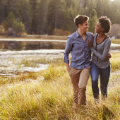 Mixed race couple embracing, walking near a rural lake