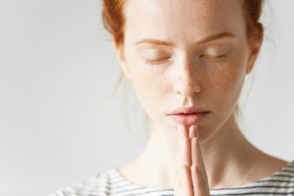 Beautiful Caucasian redhead woman praying