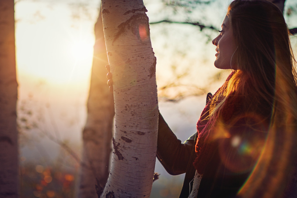 Beautiful girl is listening the music and watching last rays of sunset in the autumn mountain.