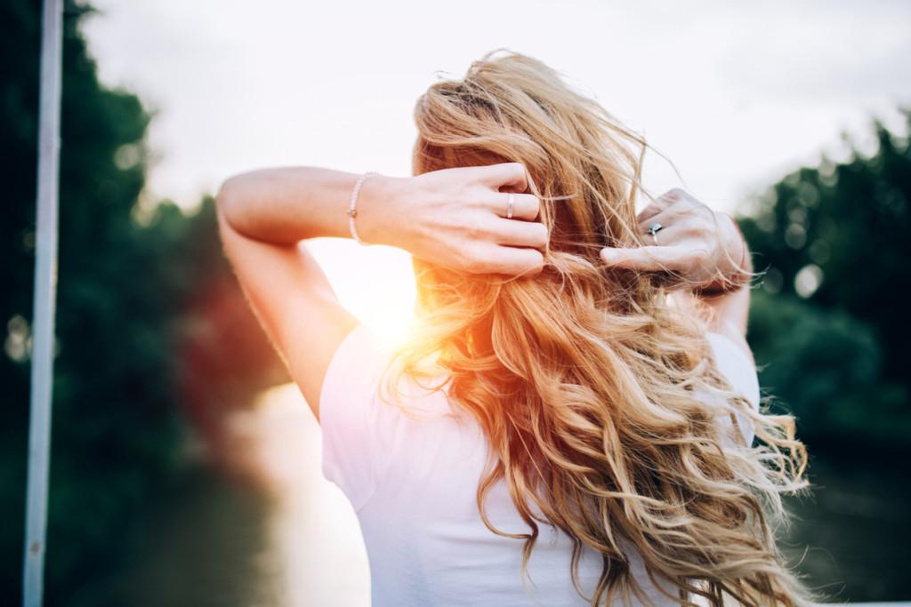 Beautiful blonde woman on the bridge.Sunset.Dusk .River.Blond girl standing at the bridge