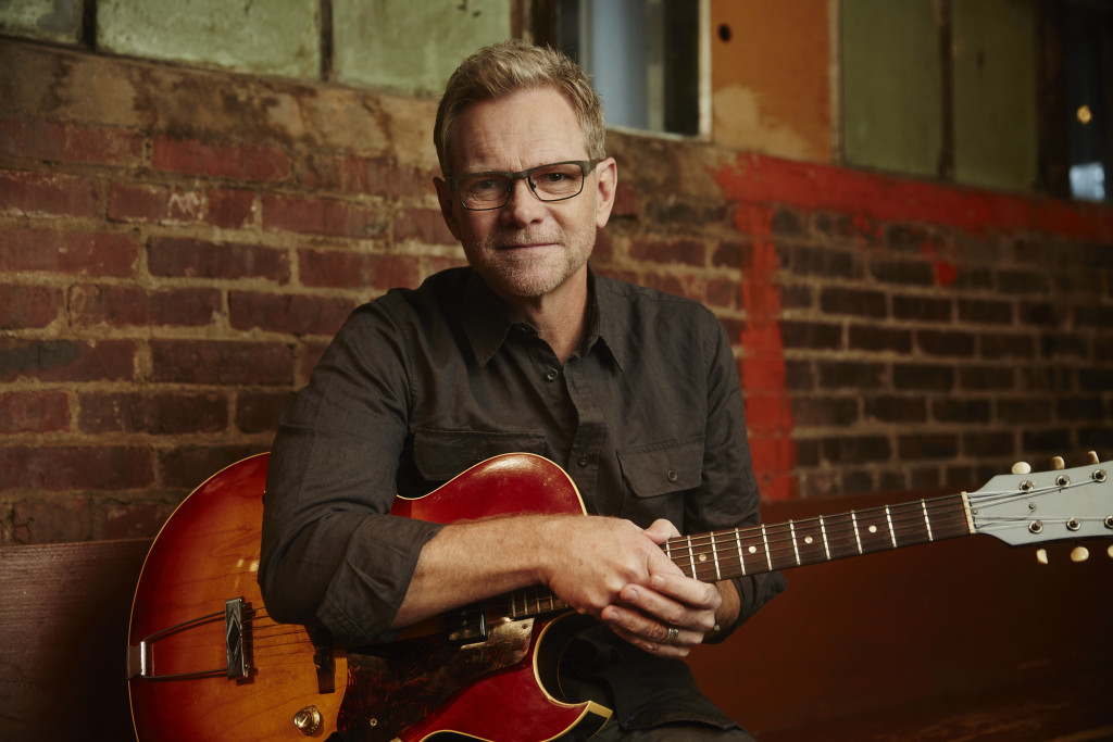 musician Steven Curtis Chapman holding a guitar in front of a brick wall