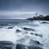 A long exposure of the waves washing over the rocks near the lighthouse at Portland Head, Maine.
