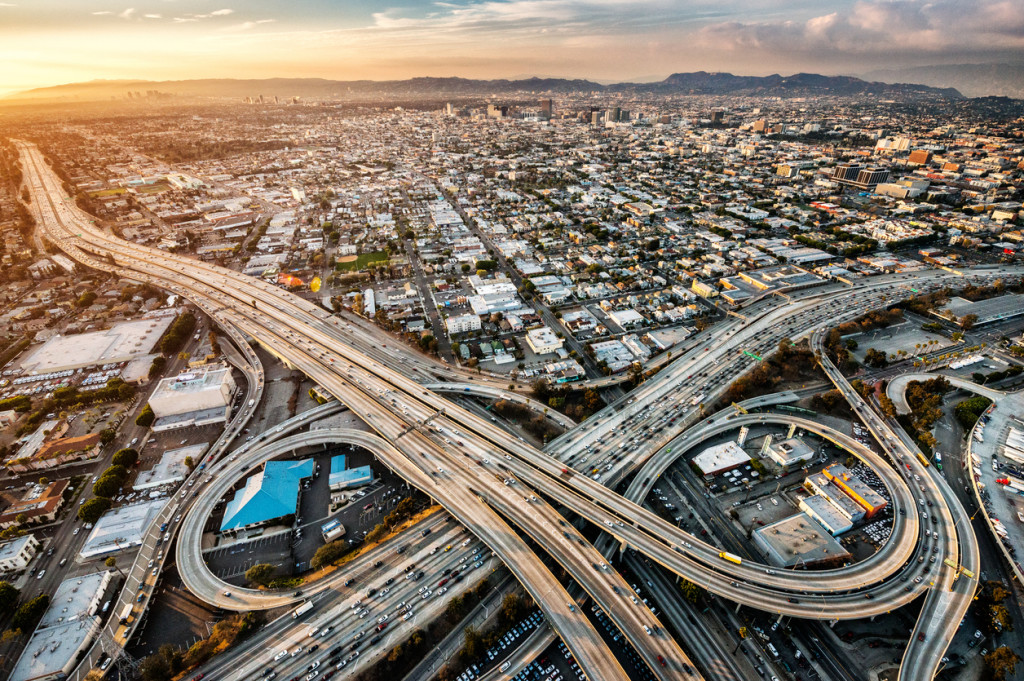 Helicopter point of view of Los Angeles highway interchanges at golden hour. Many details are visible in the image.