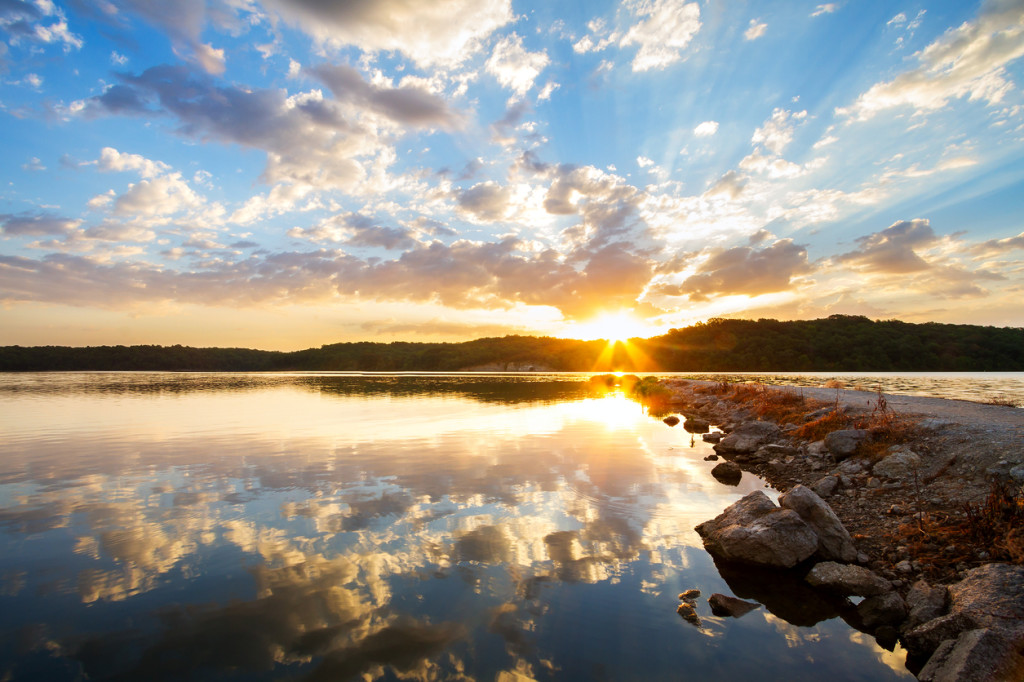 A dramatic sunrise along a rock jetty over a lake outside of Kansas City, Missouri.