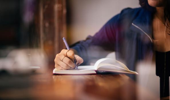 Woman Writing Journal at Window Seat in Coffee Shop