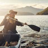 Shot of a young woman rowing a boat out on the lake