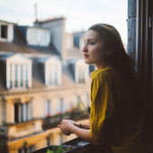 Young woman relaxing on the balcony of her Montmartre apartment