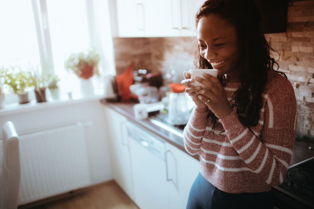 Smiling young woman enjoys cup of coffee in her kitchen, early in the morning