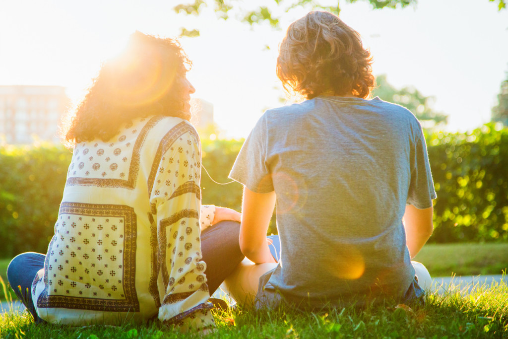 Rear view of mother sharing music sitting with teenager son in a park. Back lit by sunset, heavy lens flare.