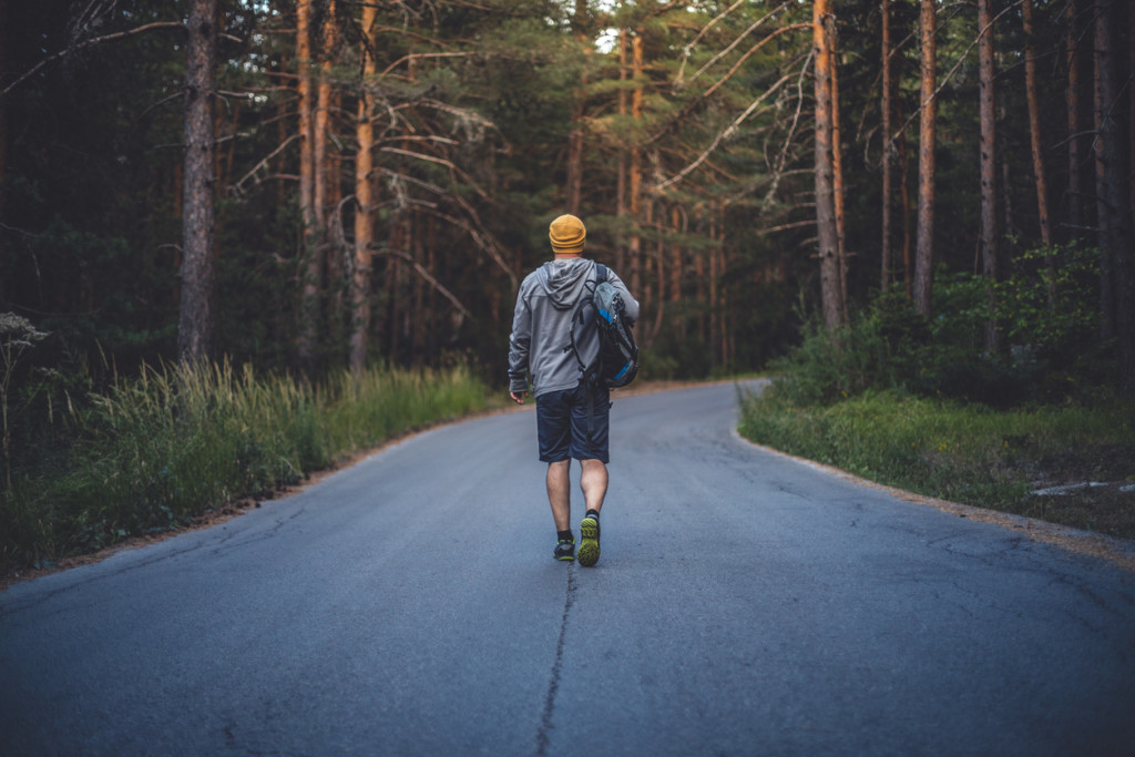 Backpacker walks alone by the road in forest