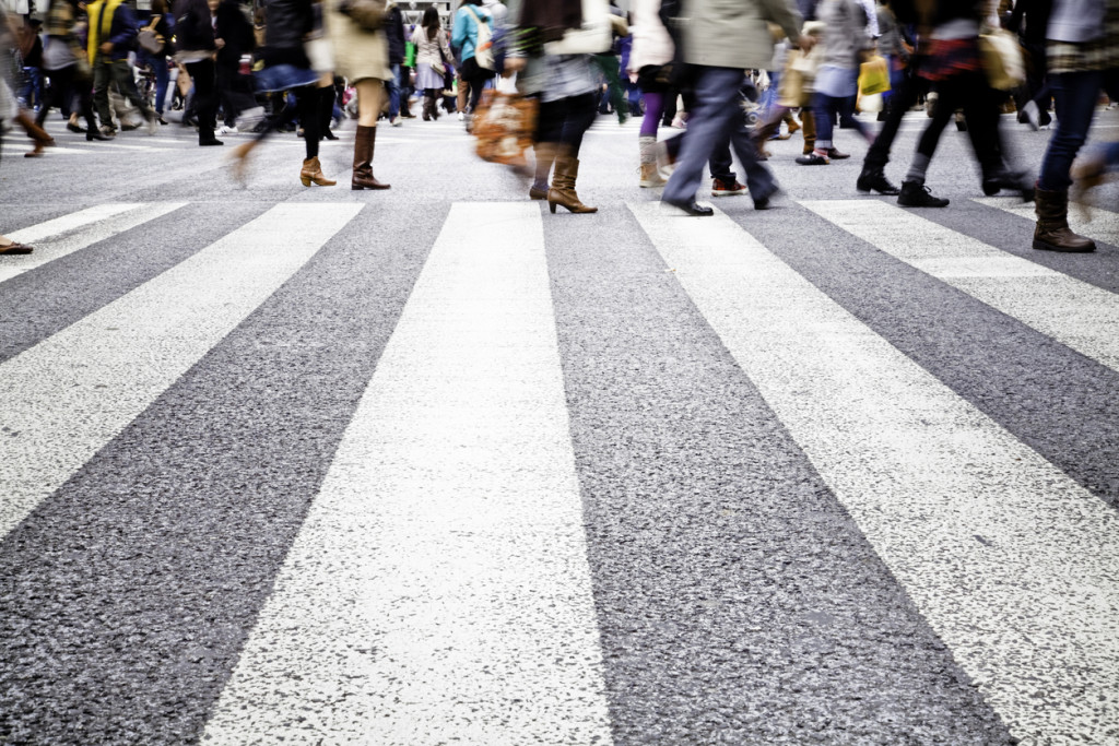 Large zebra crossing in the city, busy blurred people in the background. S