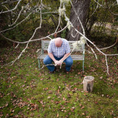 A depressed aging man sitting on a bench in Fall with his head hung low.