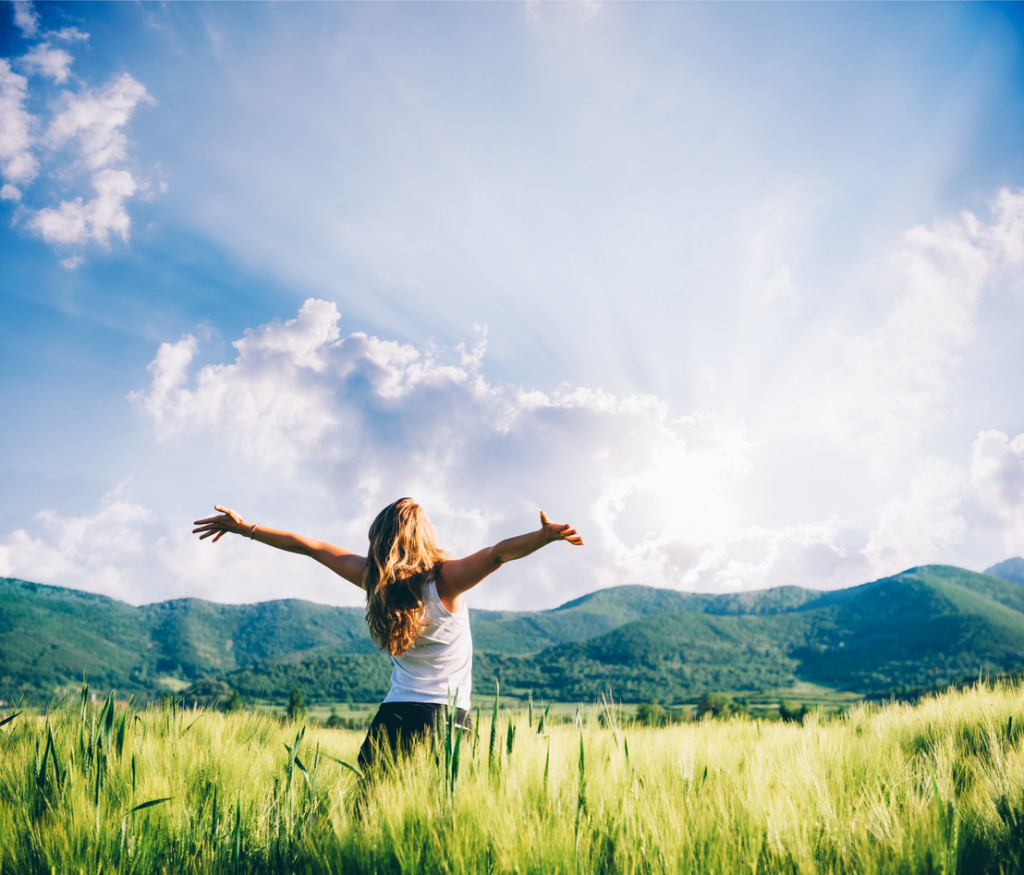 young woman in wheat field with hands outstretched towoards the sun