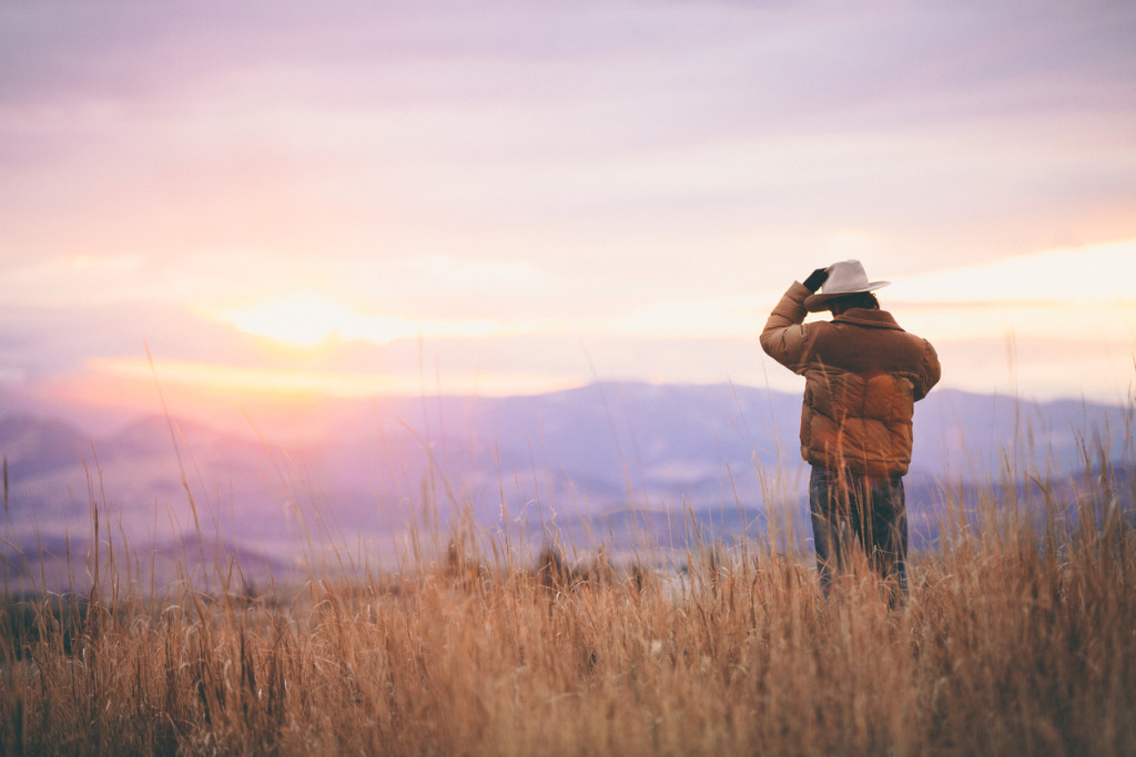 Cowboy talks on phone while watching sunset over mountains