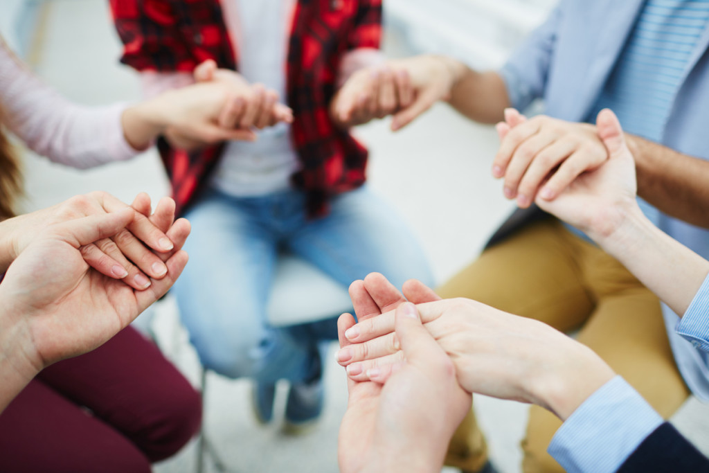 Circle of groupmates holding by hands at psychological session