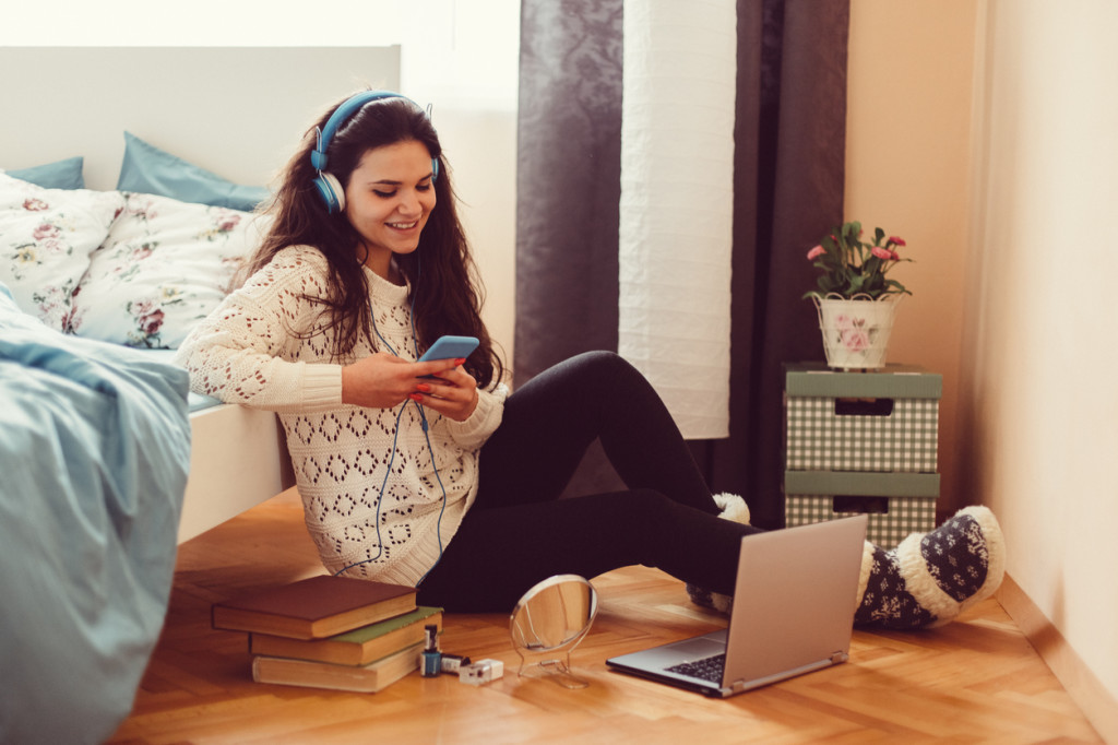 Girl at home text messaging on smartphone