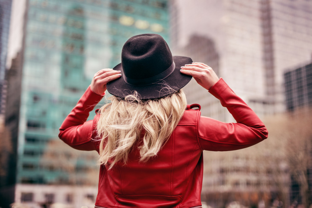 A young woman wearing a hat is walking on the streets of New York City