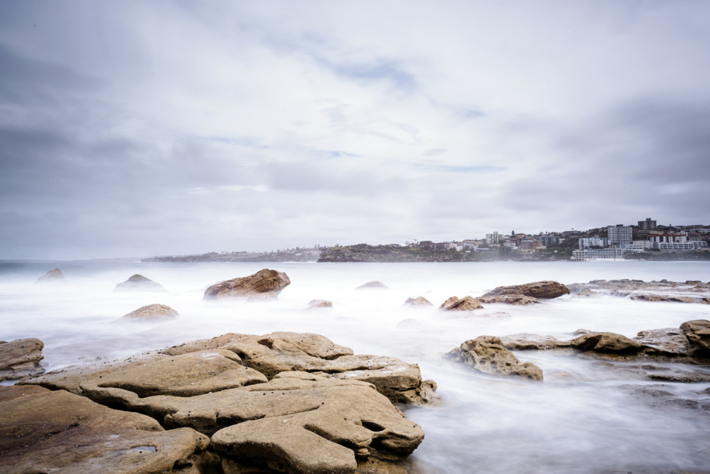 Landscape of mist over rocks in the sea on a cloudy stormy day in Sydney Australia.
