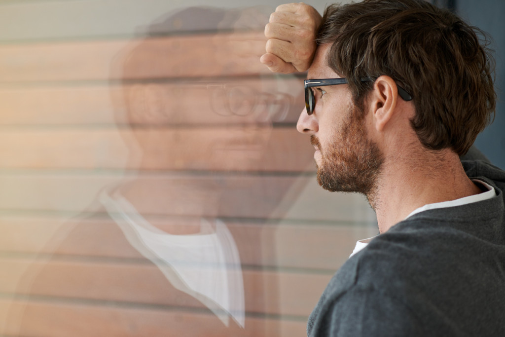 Shot of a thoughtful young entrepreneur leaning against a glass window in his office