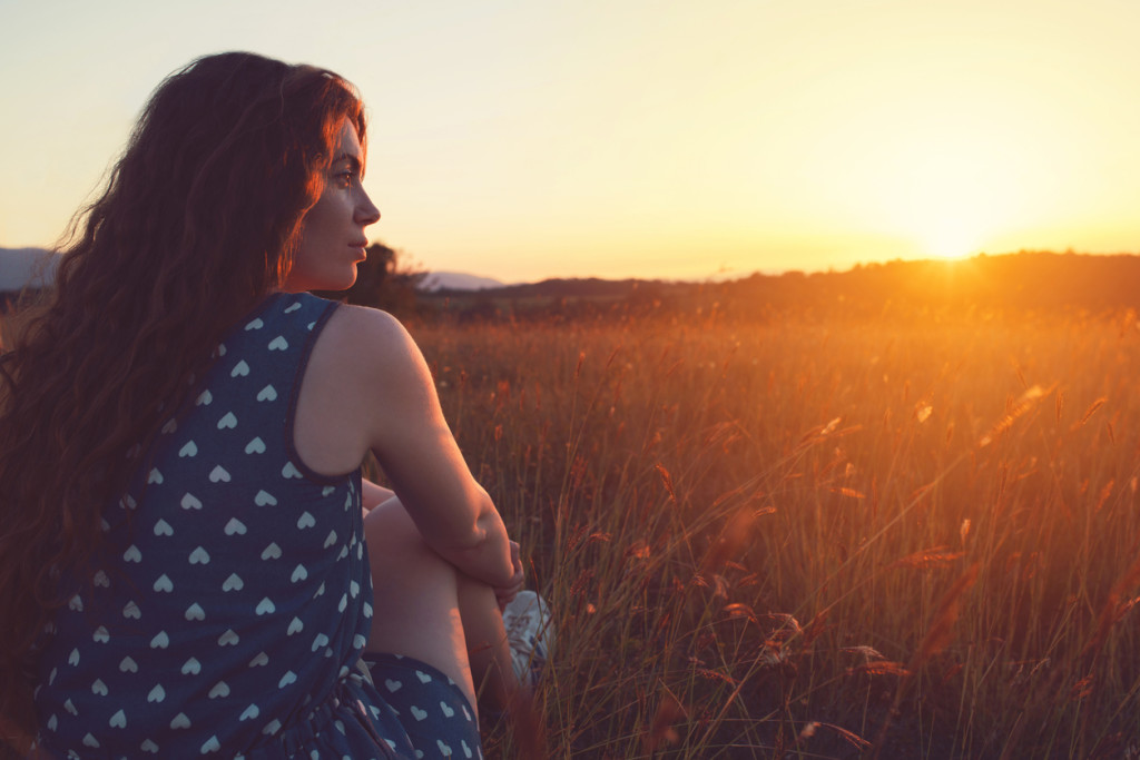 Beautiful young woman sitting in the grass, enjoying the sunset view.