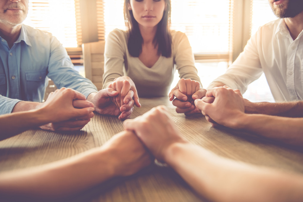 team holding hands and praying while sitting in office
