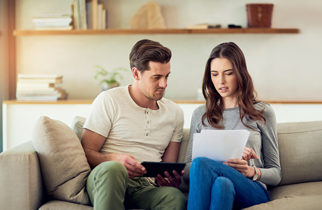 Shot of a young couple going through their paperwork together at home