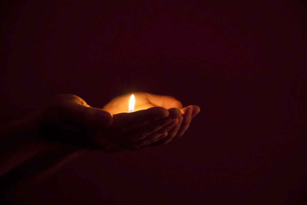 burning candle in human hands in darkness