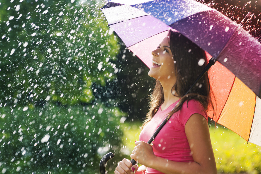 woman laughing with umbrella in rain and sunshine