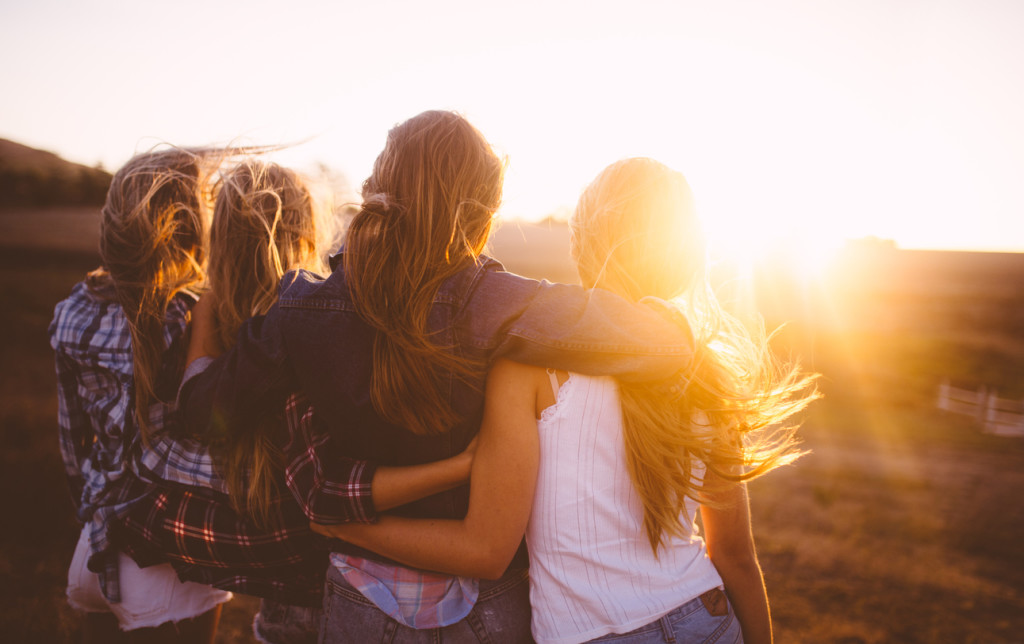 Rearview of teen girl friends looking at the sunset together on a golden summer evening