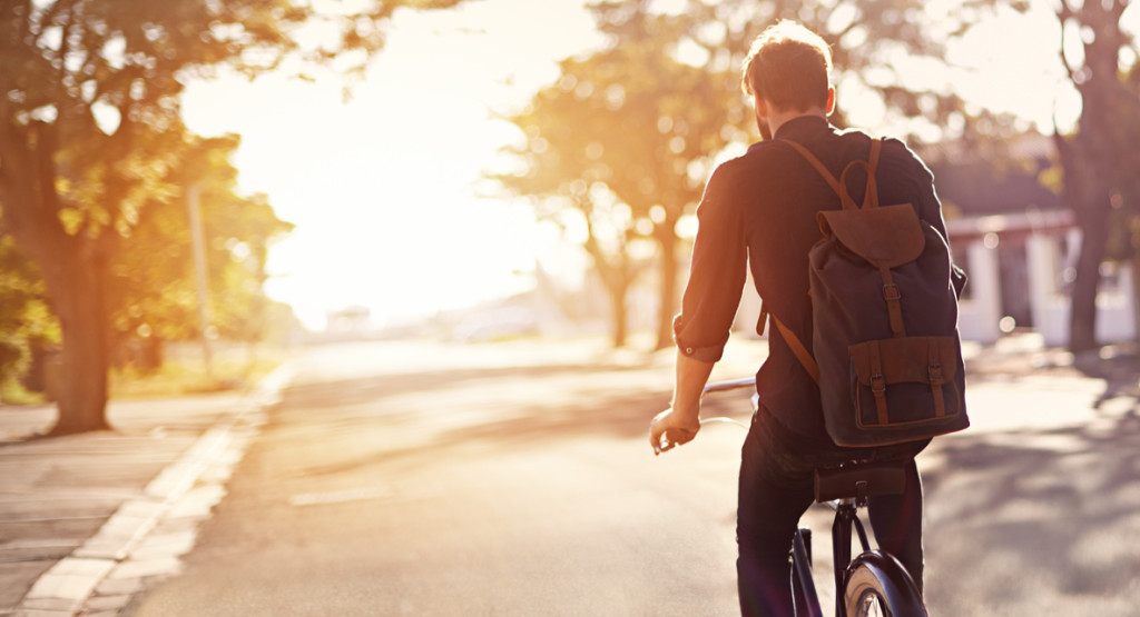 Rearview shot of a young man riding a bicycle
