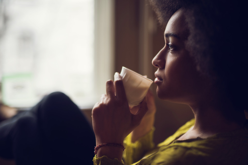 Young pensive African American woman drinking coffee and looking away.