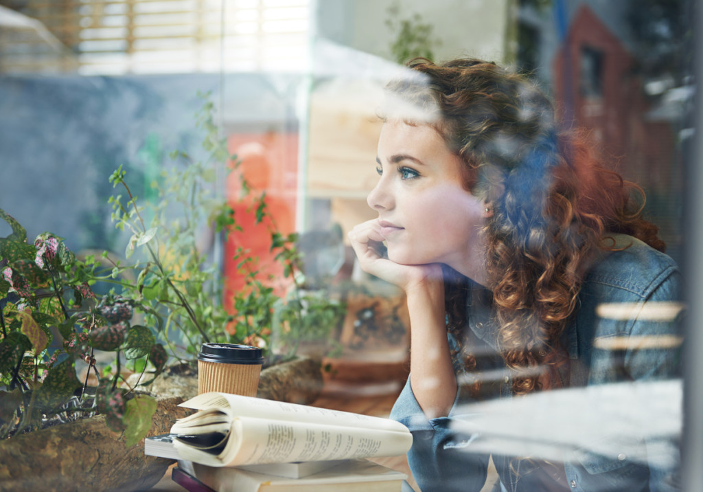 A young woman looking thoughtful while reading a book in a coffee shop