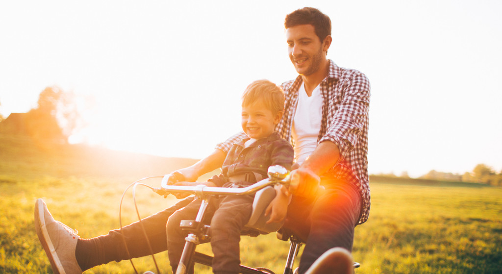 Father and his son cycling together outdoors