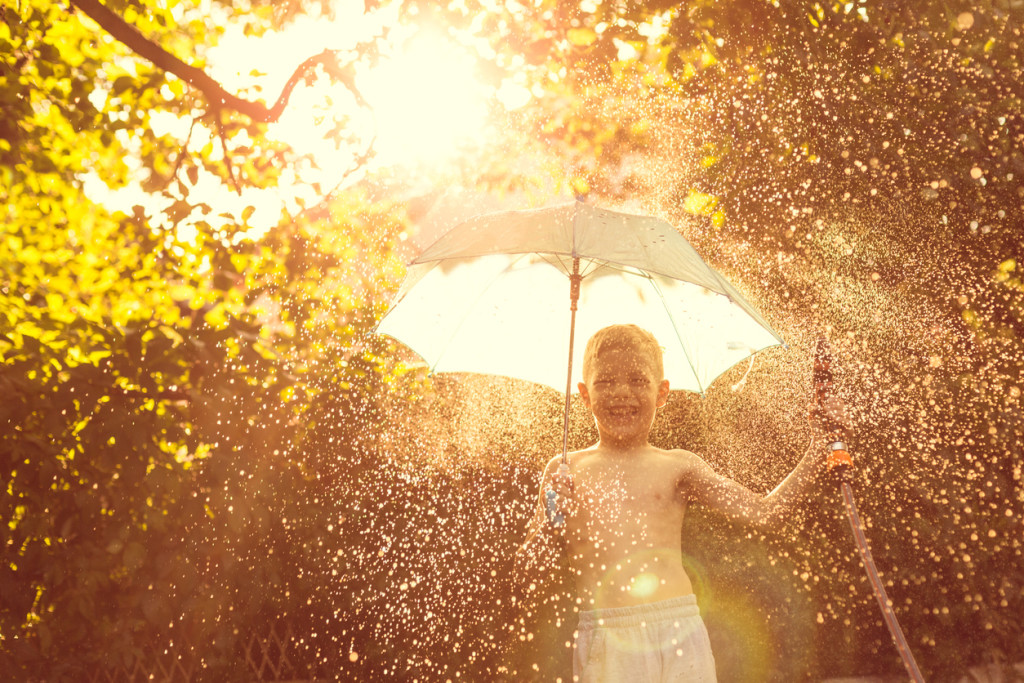 Boy splashing with water in garden