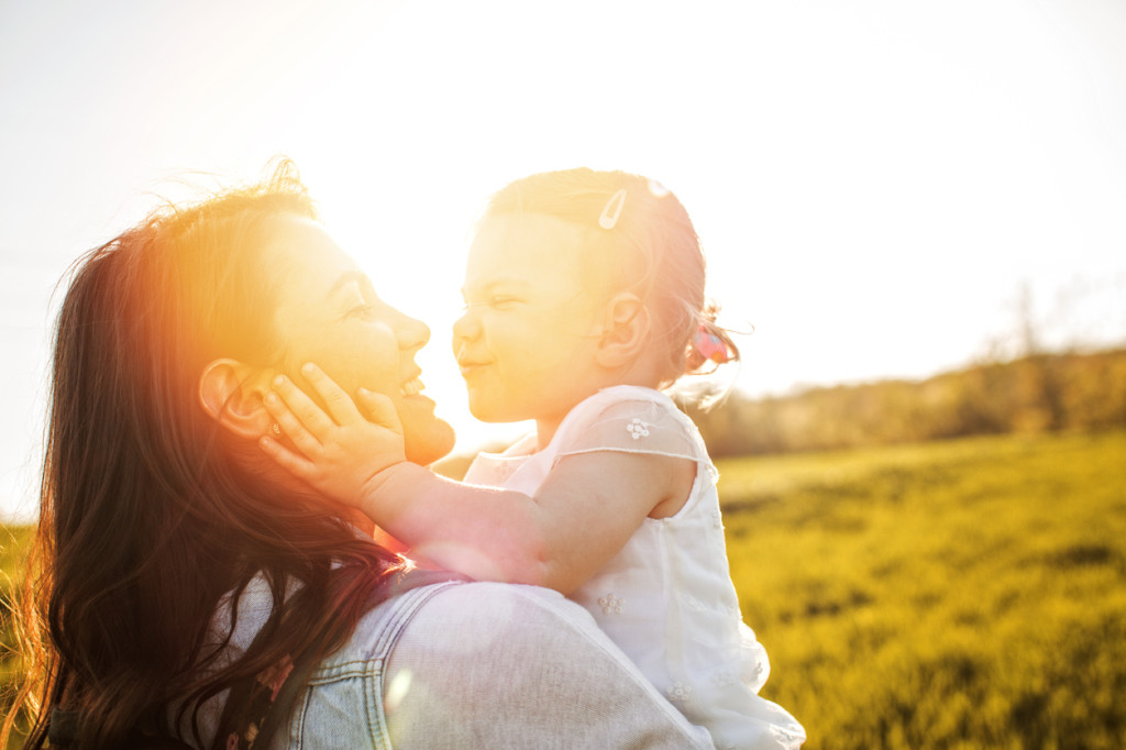 Smiling mother and her baby girl on a field on a bright sunny day