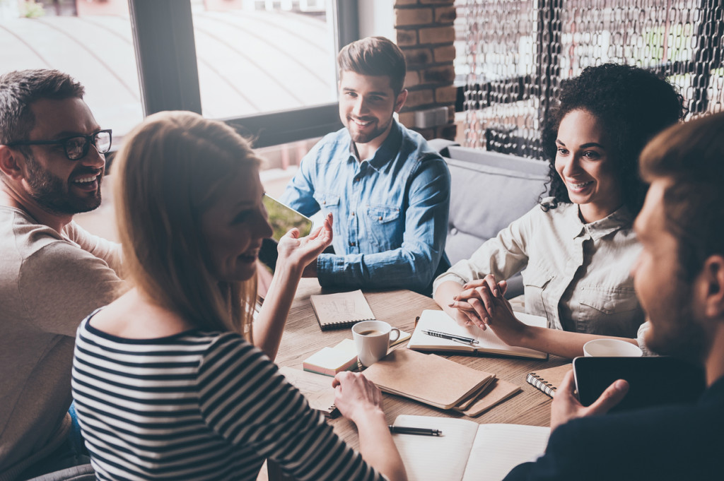 Cheerful young people looking at each other with smile while sitting at the office table at the business meeting