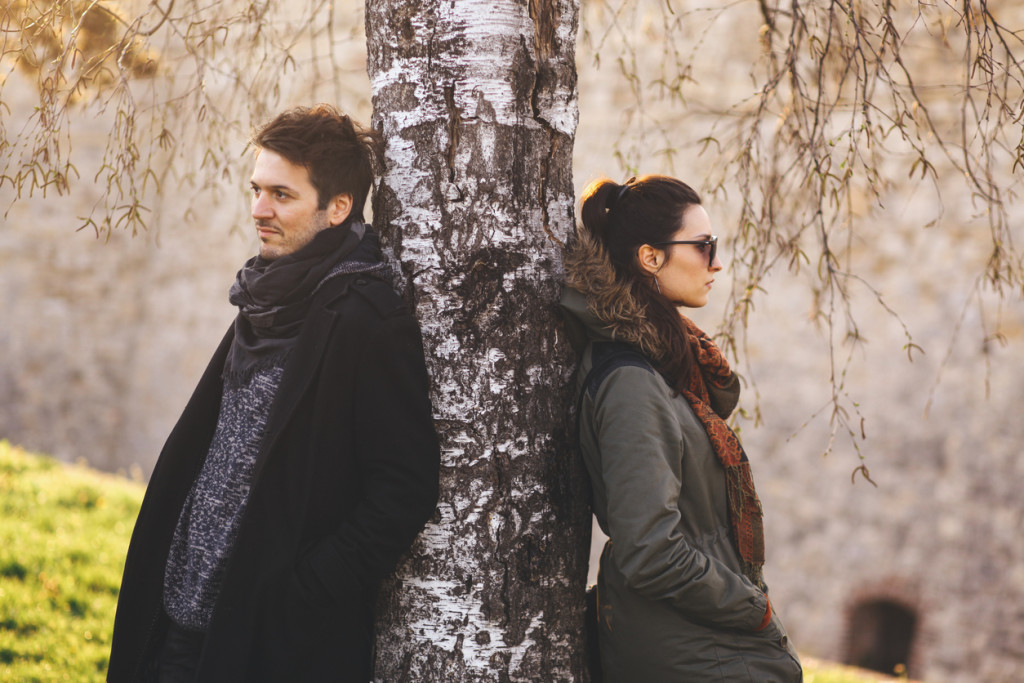 Young couple leaning on a tree in the park