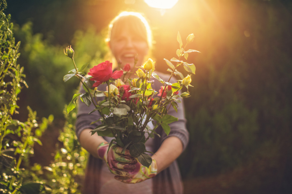 Portrait of smiling mid-adult woman who is proudly presenting flowers from her garden